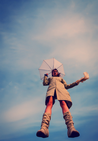 girl jumped with umbrella against the sky photo