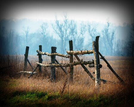 Rural landscape autumn trees and old wooden fence on the background of trees photo