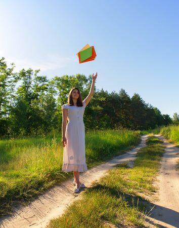 threw: girl joyfully threw sheets of paper on a sunny day