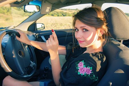 manejando: mujer conduce un coche al aire libre