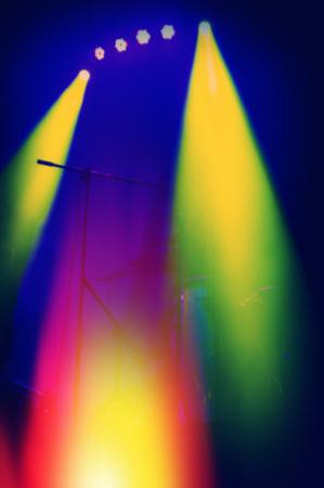 illuminating: blurred background, spotlights illuminating the concert stage