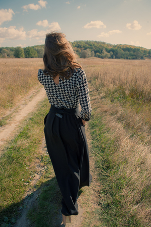 young woman walking along a country road autumn day Stock Photo