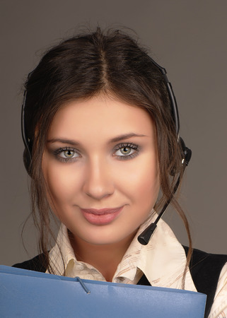 portrait of a beautiful business woman in headphones with a microphone photo