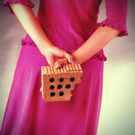 woman holding a brick behind