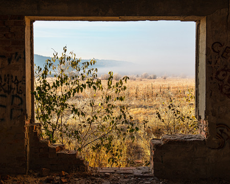 window opening: view on a rural landscape from the window opening of the destroyed building