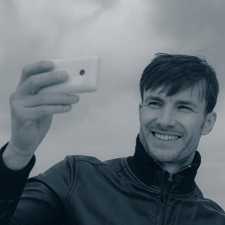 doing: businessman doing selfie smartphone outdoors
