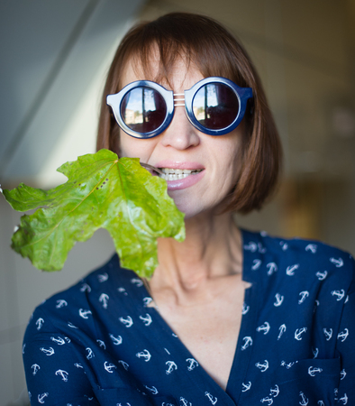 age forty: portrait of a woman with glasses and a green leaf, the age of forty years