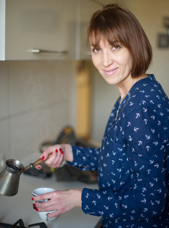 age forty: Woman brews coffee, age forty years