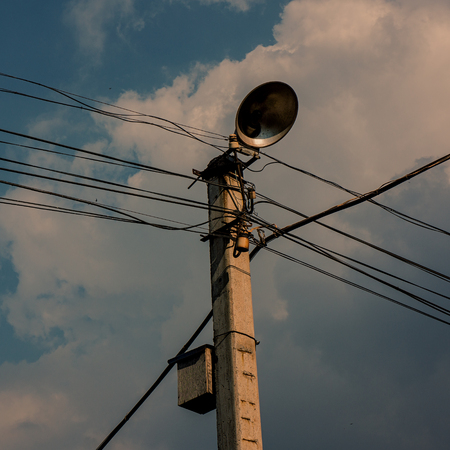 Pole of the power lines of communications on a blue sky background