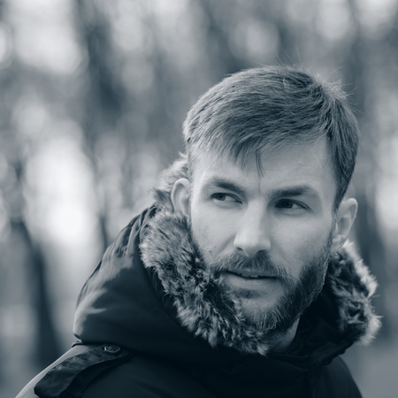 Man With A Beard Corrects His Hood And Looks Away On A Blurred Background Of Trees. Portrait Man. Bearded Man.