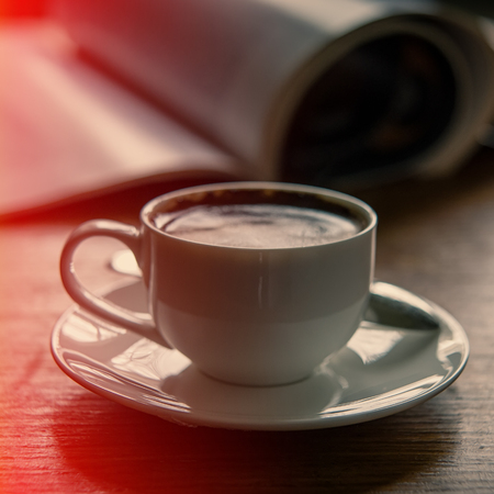 cup of coffee on the background of an open magazine. A cup on the table is indoors. Stock Photo