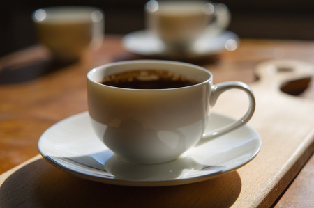 cup of freshly brewed coffee on a blurry background of two cups. Wooden table in the room.