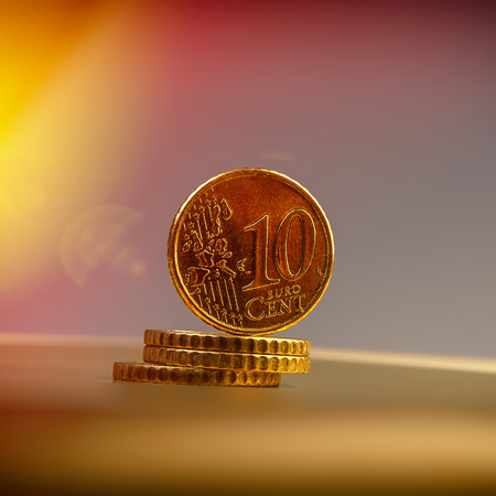 coins of ten euro cents lie on a pile of coins. Coins on the blurred background. Currency of the European Union.