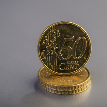 coins of fifty euro cents lie on a pile of coins. Coins on the blurred background. Currency of the European Union. Stock Photo