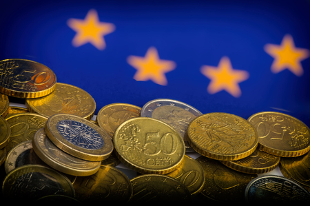 coins of euro and euro cents against the background of the flag of the European Union. Business metaphor. Conceptual.