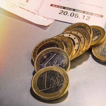 coins one euro and the checks lie on the table. Closeup. Currency of the Euro Union. 스톡 콘텐츠