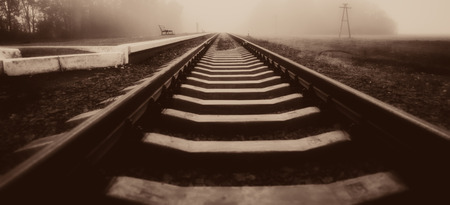 blurred rails of the railway station at the station. Autumn season, in the countryside. Panoramic and web banner format.