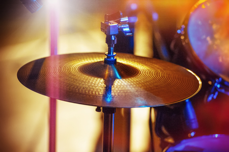 Drums and cymbals, concert performance concert, selective focus on equipment. A musician playing with chopsticks on percussion instruments. Фото со стока