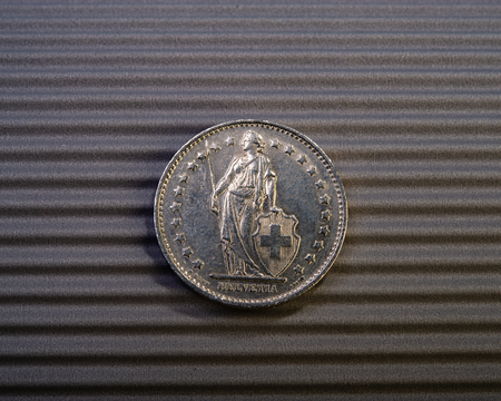 Swiss coin is two francs on a gray background.