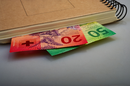 Swiss banknotes are fifty, ten, twenty francs and a notepad. Cash.
