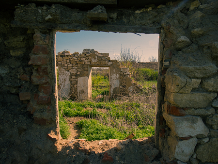 DESTROYED FORGED OLD HOUSE IN THE RURAL LOCATION. REMAINS OF WALLS AND WINDOWS.
