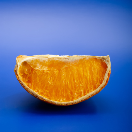 withered piece of orange lies on a blue background.  Promotion, Marketing, SMM, CEO, Business