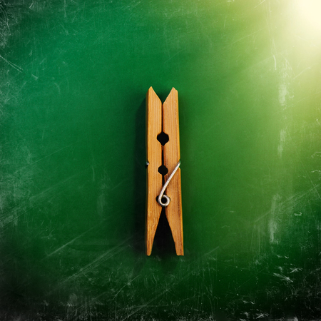 One Wooden Clothespin on a Green Background, Scratches and Scrapes. Promotion, Marketing, SMM, CEO, Business