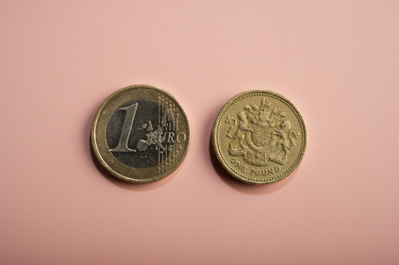 coins one euro, one pound on a pink background. Types of coins of Europe, england.