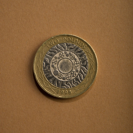 coin of two pounds on a brown background. Type of coins of England.