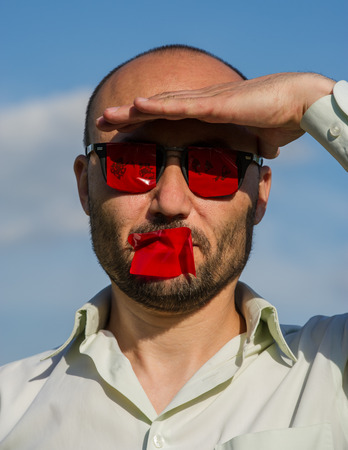 Conceptual portrait of a businessman in a goggle with glasses and mouth against a blue sky. Creative portrait of a man. Stock Photo
