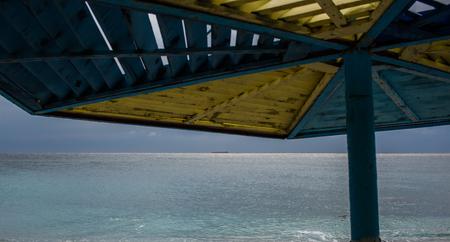 Beach umbrella and ship on the horizon in the sea, velvet season. Horizontal web banner.