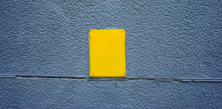 Gray plastered wall and yellow plaque. Web banner. Element of design. Stock Photo