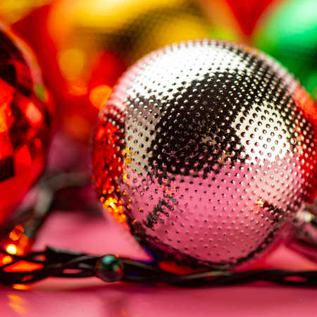 Christmas balls lie on the background of Christmas tree decorations on a pink background. Web banner. New year concept. Stock Photo