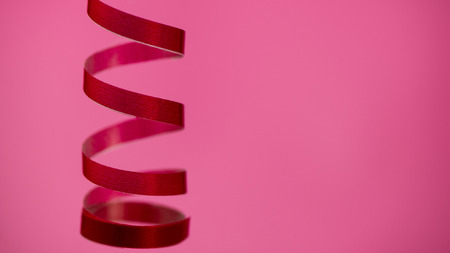 spiral of red christmas ribbon blurred pink background. Christmas composition, winter season.