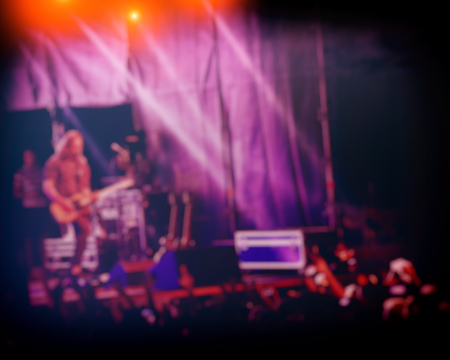 musician performs a rock band concert in the evening in the open air and fans. Concert Crowd. Rock music. Blurred  background. 版權商用圖片