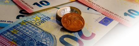 Paper notes and coins of euro and eurocents. The currency of the European Union. Web banner. 免版税图像