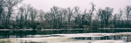 The banks of the river are covered with the remains of snow and ice and the forest is foggy in the afternoon, a panoramic landscape. Early spring. Web banner for design. Ukraine. Europe. 免版税图像