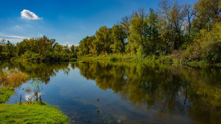 Autumn deciduous forest, water river and the river bank on a sunny day. Amazing landscape. Ukraine. Europe. Stock Photo