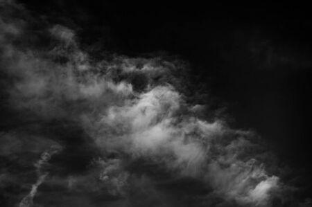 white clouds against a dark sky. Summer season, august. Monochrome photo.