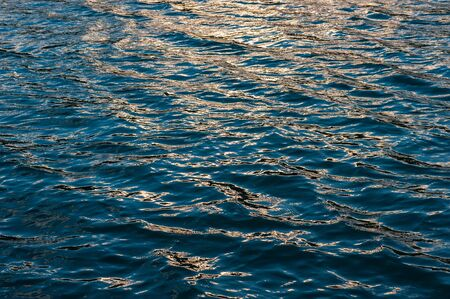 glare on the surface of the water in the sea and the waves behind the sunset. Summer season, august.