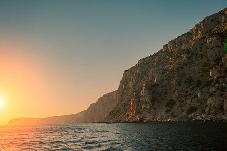 Sunset and Steep Cliffy Rocky Sea Shore. Sea and Rocks. Summer season. Ukraine.