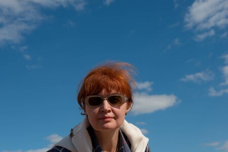 portrait of a woman in sunglasses on a background of blue sky and clouds. Age fifty five years. Autumn season, sunny day. Stock fotó - 129568091