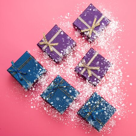 Christmas Festive Background. Blue and Purple Gift Boxes Covered in Snow on Pink Background. Web Banner.
