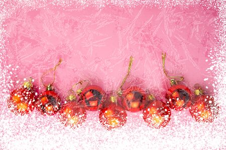 Christmas Festive Background. Snow and Hoarfrost and Red Balls on a Pink Background.