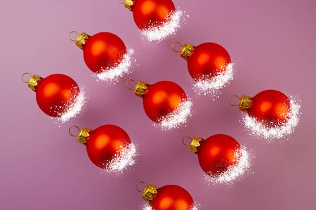 Christmas Festive Background. Christmas toys red balls in the snow on a pink background. Stock Photo