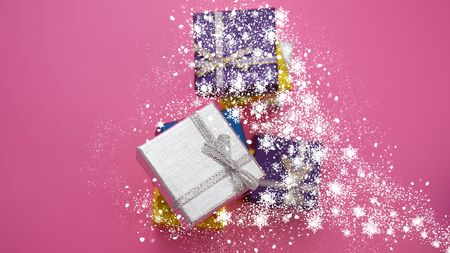 Christmas Festive Background. Silver Gift Box and Blue, Purple Boxes Covered in Snow on a Pink Background. Web Banner. Stock Photo