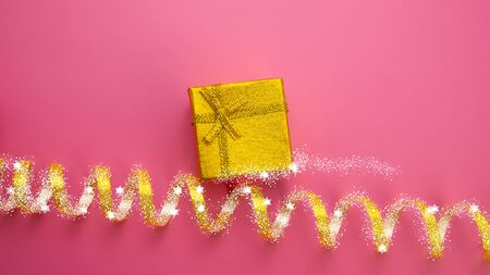 Christmas Festive Background. Golden Gift Box and Golden Ribbon Covered with Snow on a Pink Background. Web Banner. Stock Photo