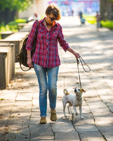 pretty woman with a dog walking in a city park in the morning. Summer season. Woman age forty-forty-five years.