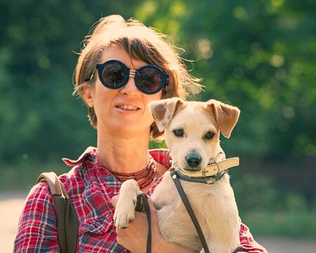 portrait of a pretty woman with a pet. Feelings of sympathy. Summer season. Woman age forty-forty-five years.
