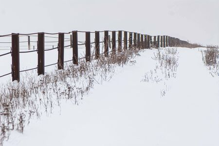 metal fence in a snow covered field. Landscape in the countryside. Winter season, january.